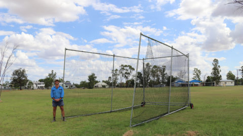 Inland Rail Community Sponsorships and Donations program recipient, Yelarbon Yellow Bellies Secretary standing in front of their new portable cricket nets